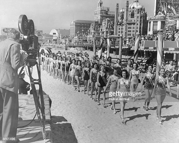 Fulllength image of a cameraman filming contestants in the Miss America Pageant as they walk on the beach next to the boardwalk at Atlantic City New...
