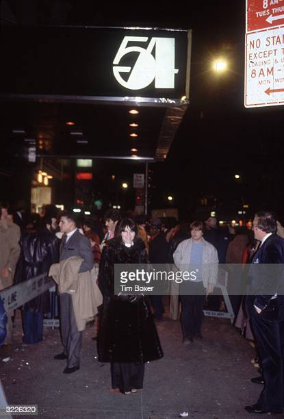 Fulllength image of a crowd standing in front of a barricade while waiting to be admitted into Studio 54 a nightclub in New York City The sign for...