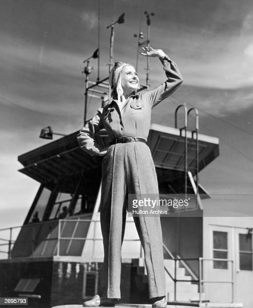 Fulllength image of a female pilot looking and gesturing towards the sky in front of a control tower at an airport She wears a cap goggles a...