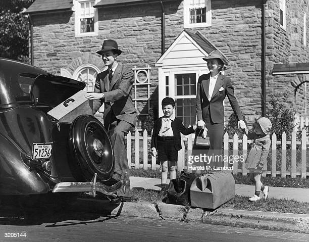 Fulllength image of a man placing a suitcase in the trunk of the family car while his wife holding the hands of their son and daughter watches from...