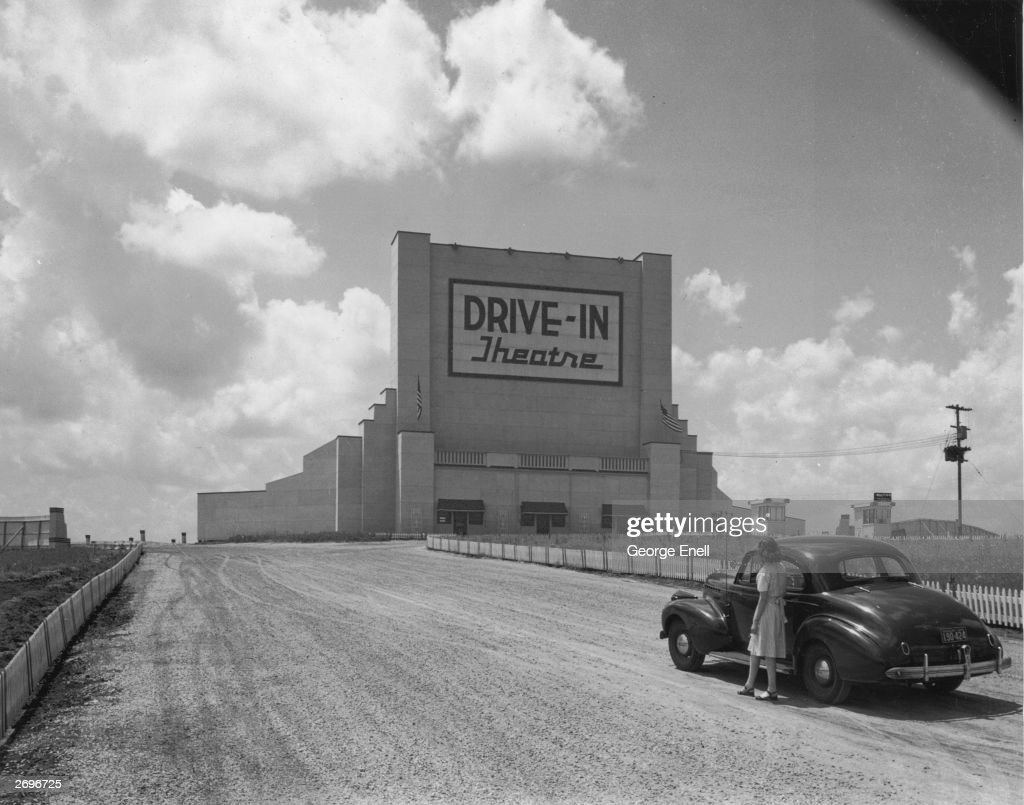 Full-length image of a woman standing next to a parked car in the middle of the road, looking up at a sign that reads, 'Drive-In Theatre'.