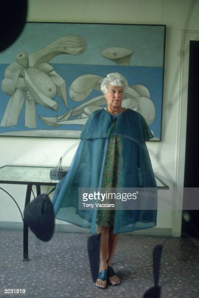 Fulllength image of American art collector Peggy Guggenheim standing in front of a Picasso painting 'On The Beach' at the Peggy Guggenheim museum...