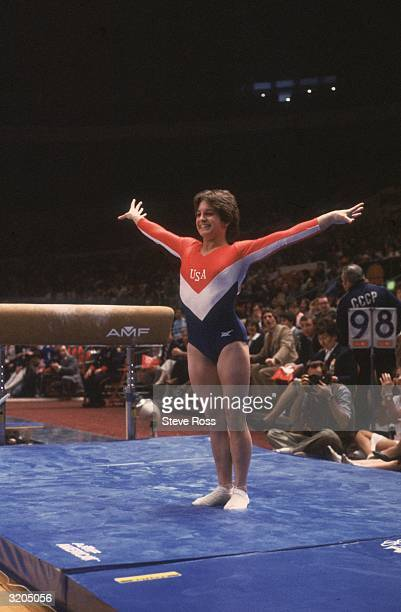 Fulllength image of American gymnast Mary Lou Retton smiling while posing on the mat after her dismount from the balance beam at the Summer Olympic...