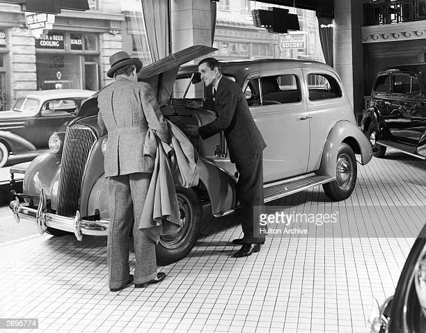 Fulllength image of an automobile salesman showing a prospective customer the interior of a new car's engine in an automobile showroom