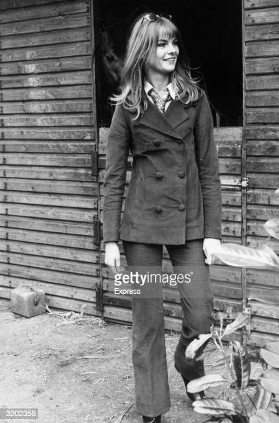 Fulllength image of British model Jean 'The Shrimp' Shrimpton smiling while standing in front of a stable on her farm in England Shrimpton wears a...