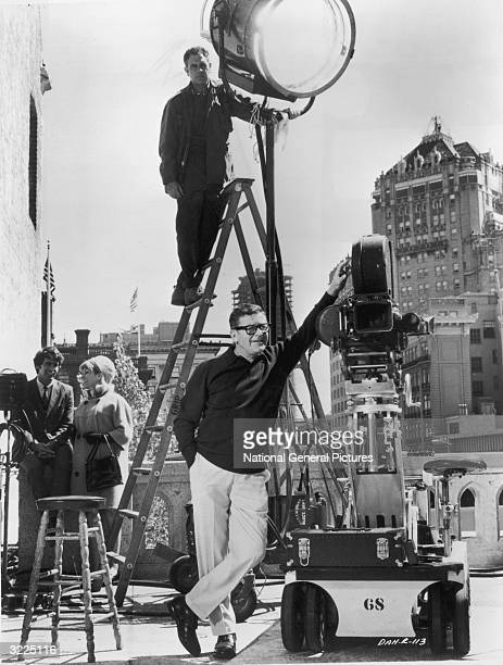 Fulllength image of Canadian film director Mark Robson standing outdoors beside a motion picture camera on location for his film 'Daddy's Gone...
