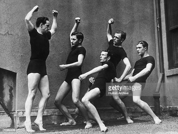 Fulllength image of five men dressed in matching black Tshirts and shorts contorting their bodies while exercising possibly on a rooftop 1910s The...