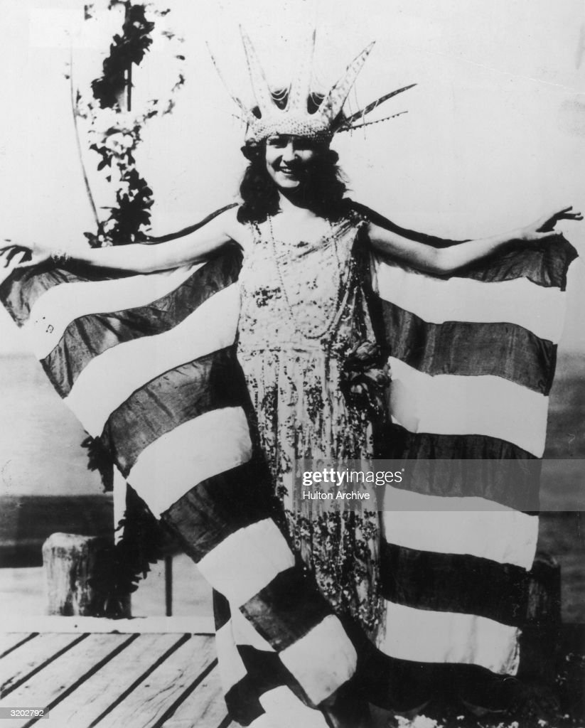 Fulllength image of Margaret Gorman from Washington DC smiling wearing a large Statue of Liberty crown and a striped cape as the first Miss America...