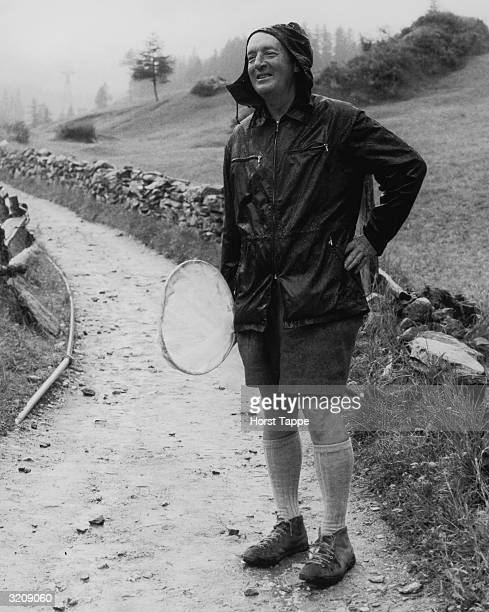 Fulllength image of Russianborn novelist Vladimir Nabokov carrying a net while hunting for butterflies in the rain Zermatt Switzerland