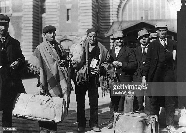 A fulllength image of Sicilian immigrant men wearing numbered tags on their coats and standing with their luggage at Ellis Island New York City