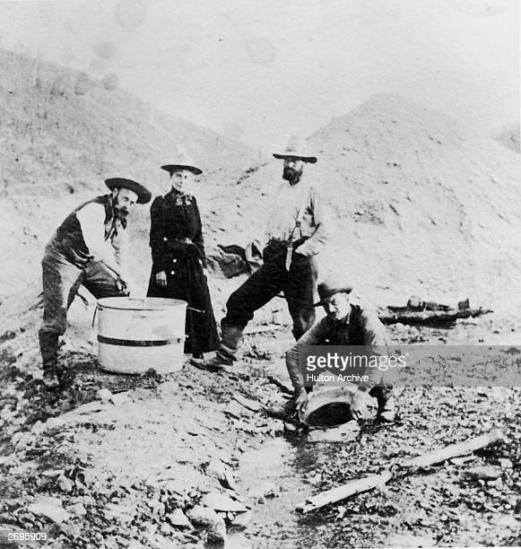 Fulllength image of three men and a woman standing and crouching around a riverbed while panning for gold during the Klondike gold rush Alaska