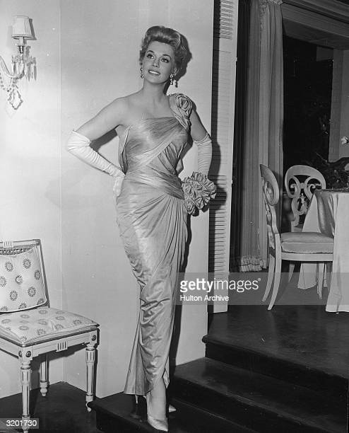 Fulllength portrait of American actor Donna Douglas posing in a formfitting draped silk gown designed by Walter Plunkett while promoting director...