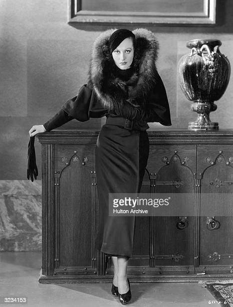 Fulllength portrait of American actor Joan Crawford wearing a long belted coat with a fur collar and a beret holding a glove over the edge of a large...