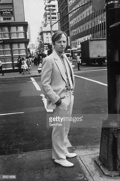 Fulllength portrait of American author Tom Wolfe in his signature white suit and shoes standing on a street corner in New York City