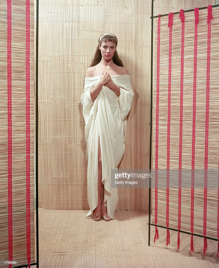 Full-length portrait of American film actor and theater producer Rita Gam clothed in classical drapery, 1950s.