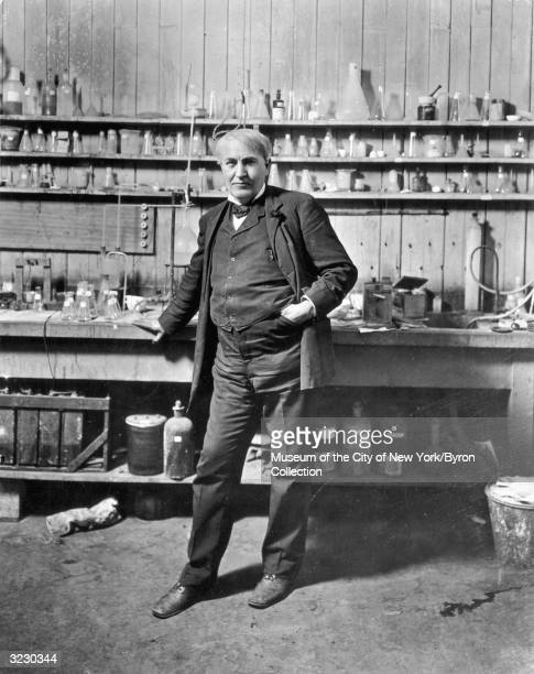 Fulllength portrait of American inventor Thomas Alva Edison standing in his laboratory Menlo Park New Jersey Beakers and jars line the shelves