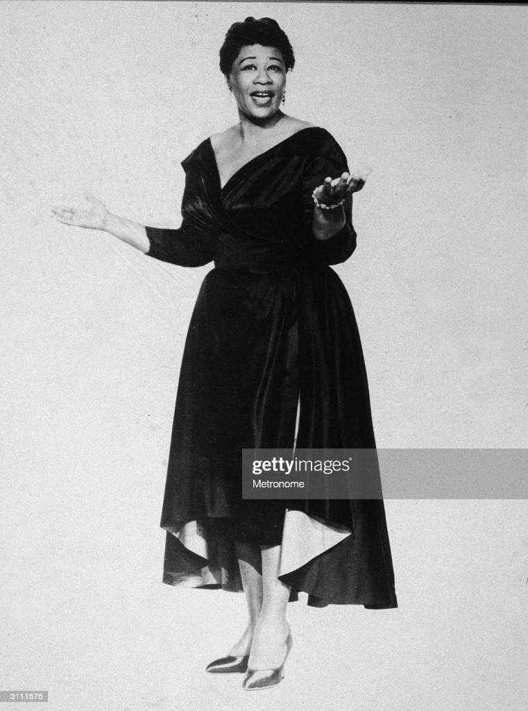 Full-length portrait of American jazz singer Ella Fitzgerald (1917 - 1996) singing and wearing a dark evening dress, 1950s.