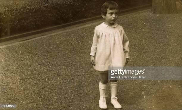 A fulllength portrait of Anne Frank standing in a white dress Aachen Germany From Anne Frank's photo album