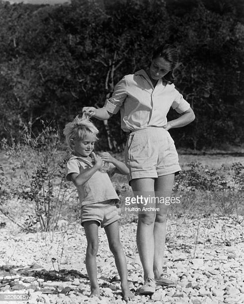 Fulllength portrait of British anthropologist and expert on chimpanzees Jane Goodall standing outdoors in shorts and running her fingers through the...
