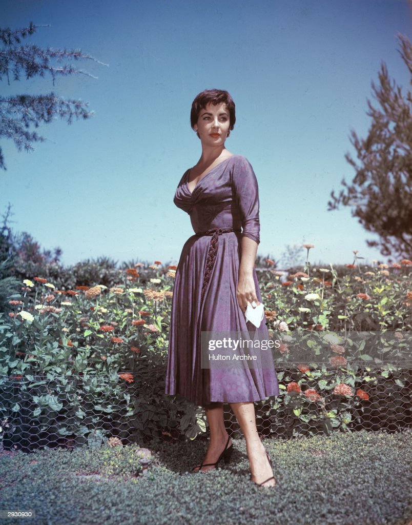 Full-length portrait of British-born actor <a gi-track='captionPersonalityLinkClicked' href=/galleries/search?phrase=Elizabeth+Taylor&family=editorial&specificpeople=69995 ng-click='$event.stopPropagation()'>Elizabeth Taylor</a> as she stands in a garden and holds a handkerchief in her right hand, circa 1950s.