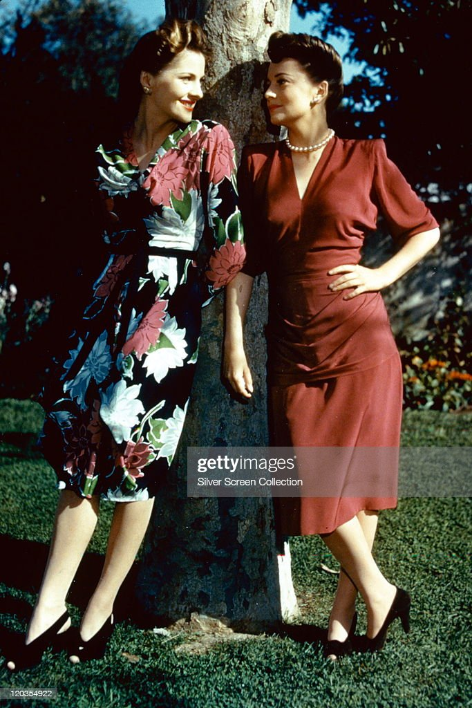 Full-length portrait of <a gi-track='captionPersonalityLinkClicked' href=/galleries/search?phrase=Joan+Fontaine&family=editorial&specificpeople=206434 ng-click='$event.stopPropagation()'>Joan Fontaine</a> (left) and her sister, Olivia de Havilland, both British actress, standing in conversation by a tree, circa 1945.