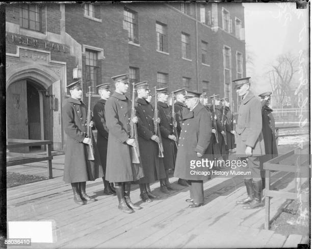 Fulllength portrait of John Philip Sousa American composer and bandmaster standing in front of a group of young men wearing military uniforms and...