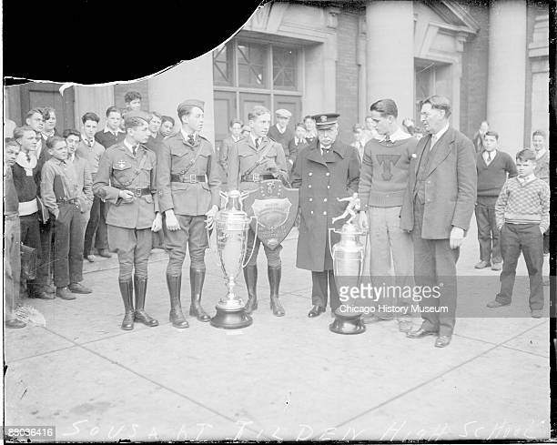 Fulllength portrait of John Philip Sousa American composer and bandmaster standing with a group of young men in front of Tilden High School located...