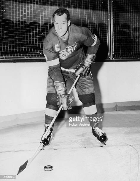 Fulllength portrait of legendary Canadian professional ice hockey player Gordon Howe of the Detroit Red Wings on the ice in uniform holding a stick...