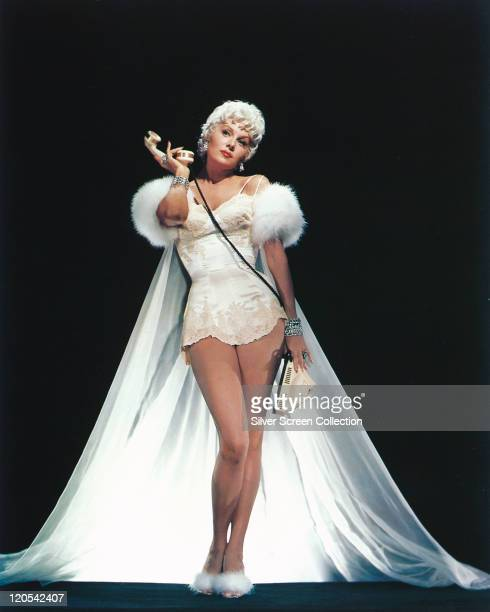 Fulllength portrait of Rhonda Fleming US actress with blonde hair wearing a white slip with a long white furtrimmed dressing gown posing with a cream...