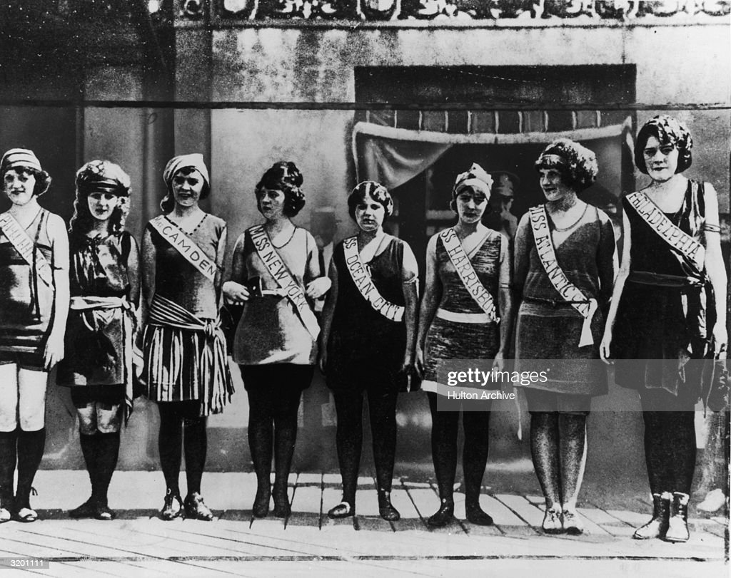 Fulllength portrait of the first Miss America contestants wearing their sashes over swimsuits standing in a line on the boardwalk in Atlantic City...
