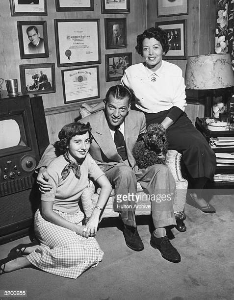 Fulllength promotional portrait of American television show host Ed Sullivan sitting in an armchair at home with his wife Sylvia their daughter Betty...