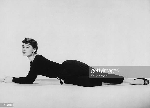 Fulllength promotional portrait of Belgianborn actor Audrey Hepburn reclining in a black pantsuit for the film 'Sabrina' directed by Billy Wilder 1954