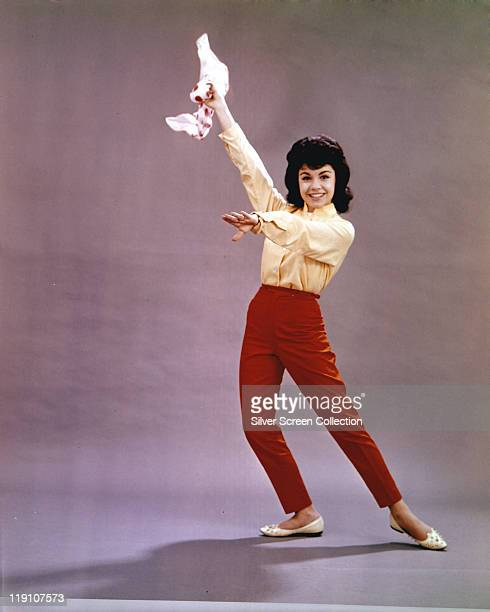 Fulllength shot of Annette Funicello US singer and actress wearing a yellow blouse and red trousers as she holds a dance pose with one up...