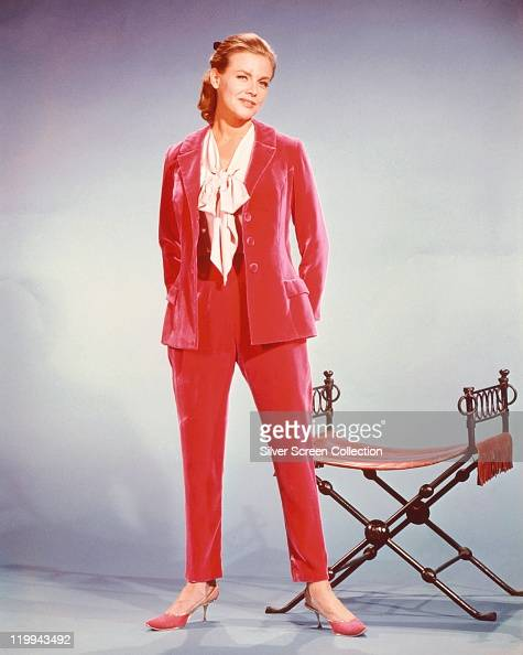 Fulllength shot of Honor Blackman British actress weaing a red trouser suit white blouse and red shoes posing beside a chair in a studio portrait...