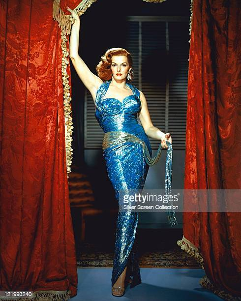 Fulllength shot of Jane Russell wearing a blue halterneck dress with a pair of red theatre curtains either side of her circa 1955