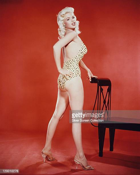 Fulllength shot of Jayne Mansfield US actress wearing a leopard print swimsuit in a studio portrait against a red background circa 1955