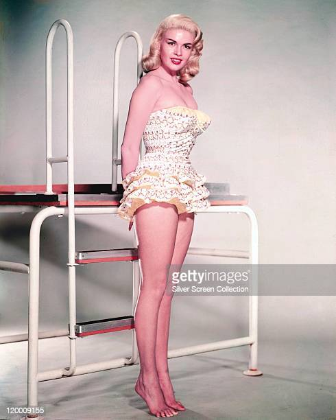 Fulllength shot of Jayne Mansfield US actress wearing a swimsuit while posing beside a swimming pool ladder circa 1955