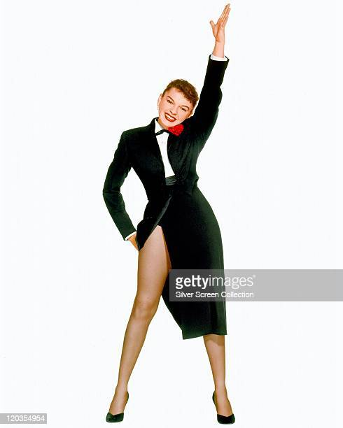 Fulllength shot of Judy Garland US actress and singer holding a pose with her feet apart and left arm raised in the air wearing a split black skirt...