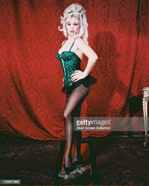 Fulllength shot of Mamie Van Doren US actress and singer wearing a greenandblack bustier in a studio portrait standing against a red curtain circa...