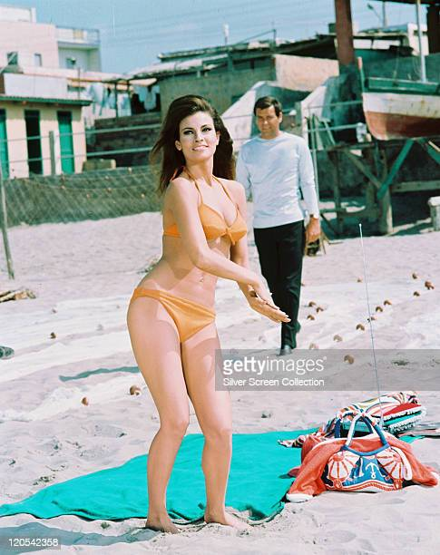 Fulllength shot of Raquel Welch US actress wearing an orange bikini while standing alongside a blue towel on a beach in a publilcity still issued for...