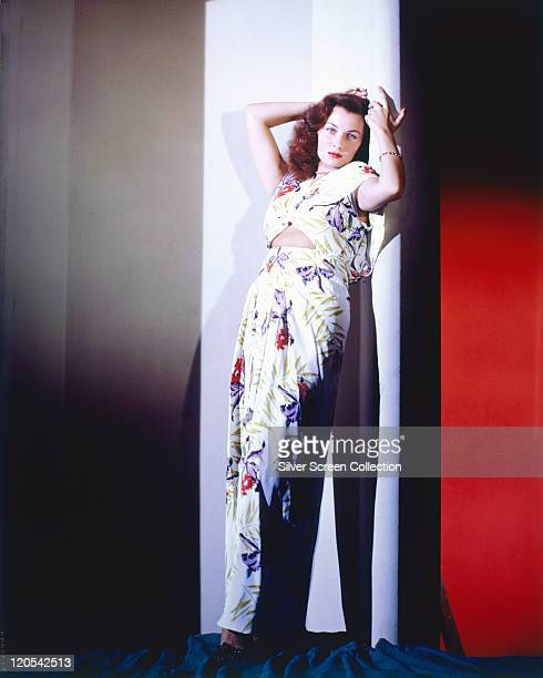 Fulllength shot of Rhonda Fleming US actress wearing a long white floral print dress posing with her arms raised to her head in a studio portrait...