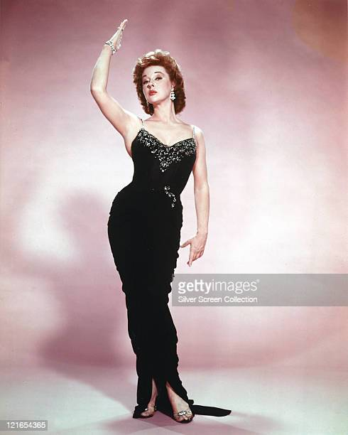 Fulllength shot of Susan Hayward US actress wearing a long black dress with a sequinned decoration across the chest posing with her right arm raised...