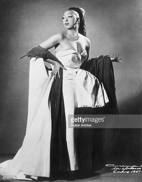 Fulllength studio portrait of American singer and performer Josephine Baker wearing a fall with her hair pulled back standing in a strapless gown...