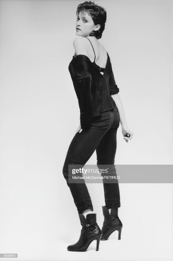 A fulllength studio portrait of future American pop singer Madonna standing in profile and looking over her shoulder in a black bra a black ripped...