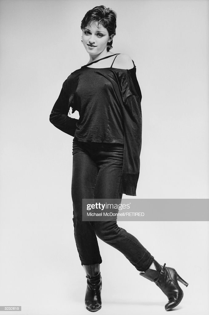 A fulllength studio portrait of future American pop singer Madonna standing knockkneed in a ripped black offtheshoulder shirt tight black Levi's...