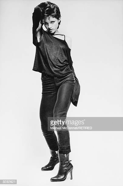 A fulllength studio portrait of future American pop singer Madonna standing with her hand behind her head and wearing a ripped black offtheshoulder...