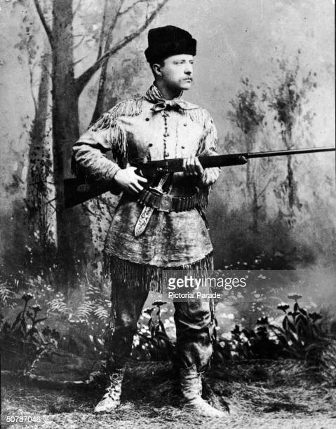 A fulllength studio portrait of Theodore Roosevelt president of the United States from 1901 to 1909 wearing hunting gear and holding a Winchester gun...