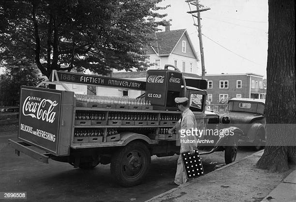 Fulllength view of a delivery man unloading cases of CocaCola from a truck bearing a sign '1886 Fiftieth Anniversary 1936'
