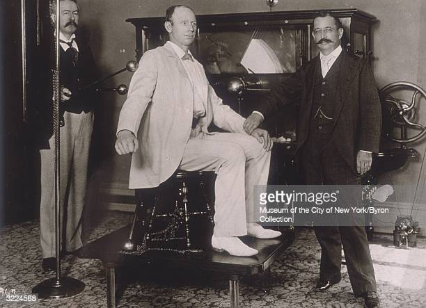 Fulllength view of British boxer Bob Fitzsimmons having his pulse taken by Dr John Woodbury while Dr John Gibbs uses electrodes attached to a machine...