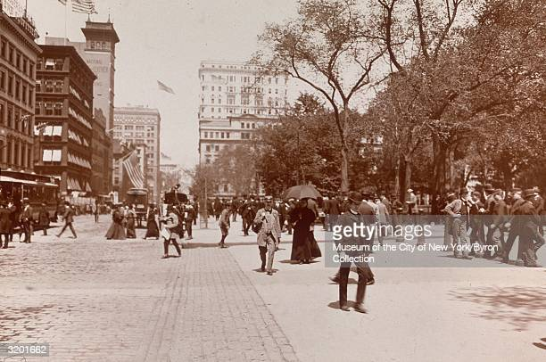 Fulllength view of pedestrians buses and horsedrawn carriages passing City Hall Park facing north on Broadway New York City